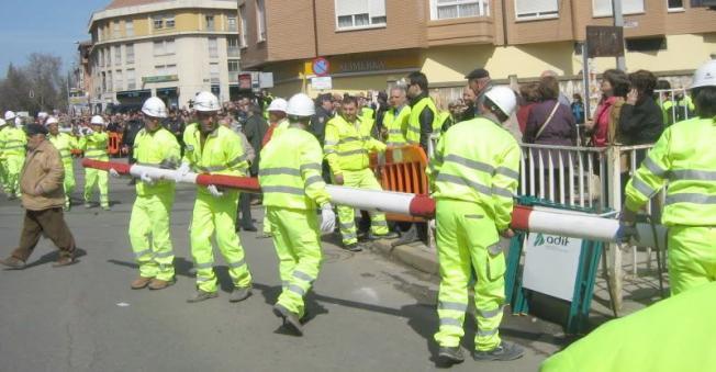 Obreros de Adif retirando las barreras del paso a nivel.